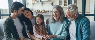 Image Happy family spending time together and smiling while sitting on the sofa at home