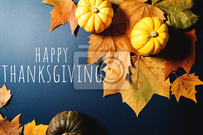 Image Happy Thanksgiving Day with maple leaves and pumpkin on blue background