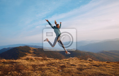 Image Happy woman hiker jumping on mountain ridge on blue cloudy sky and mountains background. Travel and active lifestyle concept.
