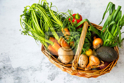Healthy organic bio vegetables in a basket with carrots, greens, onion, avocads, tomatoes, mushrooms, fresh green bio harvest