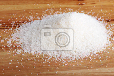 heap of coconut flakes on wooden plank