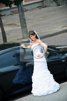 heureuse mariée en robe blanche debout près de la voiture de mariage
