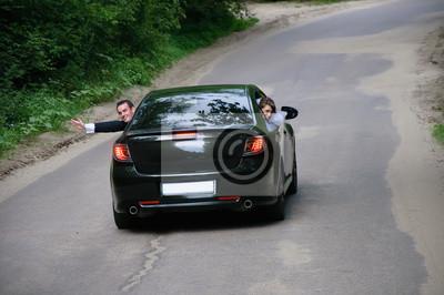 heureux mariés voyageant dans une voiture et vague mains