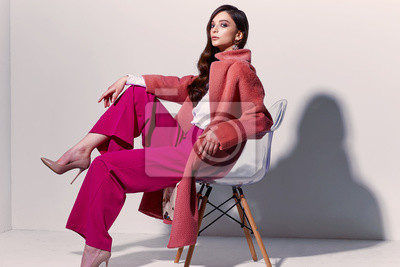 Image High fashion portrait of young elegant woman. Coral coat, magenta pants, white blouse.