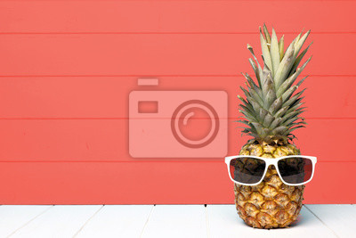 Image Hipster pineapple with sunglasses against a living coral colored wood background. Minimal summer concept.