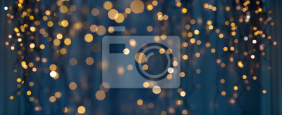 Image holiday illumination and decoration concept - christmas garland bokeh lights over dark blue background