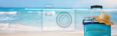 Image holidays. travel concept. blue suitcase with female hat, flipflops in front of tropical marina background