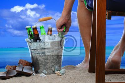 Homme à la plage avec un seau de bière