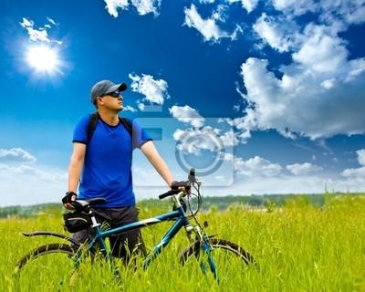homme avec le vélo sur terrain vert