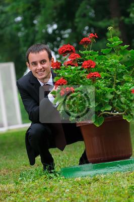 homme élégant en costume assis près de buisson de fleurs