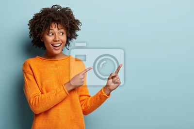 Image Horizontal shot pleased dark skinned female with Afro haircut, points away with both fore fingers, shows blank space for your promotion, isolated over blue background. People, advertisement concept