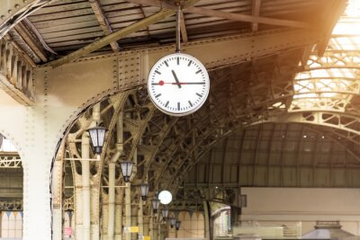 Image Horloge vintage sur la gare avec toit de bâtiment.