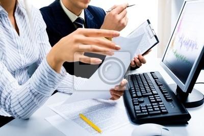 Image de deux partenaires d'affaires discutant documents