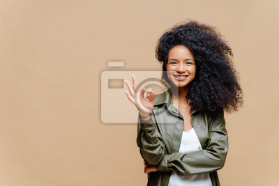 Image Indoor shot of pleasant looking curly woman has pleasant smile, makes okay gesture, excellent sign, gives approval, dressed in fashionable leather shirt, isolated over brown wall, blank space on left