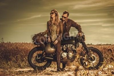 Image Jeune, élégant couple café racer sur les motos custom vintage dans un champ.