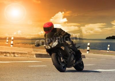 Image Jeune homme à la grande moto à vélo contre une courbe pointue d'asphalte route haute route avec paysage rural utilisation de scène pour les activités d'aventure masculine et le sport automobile sport