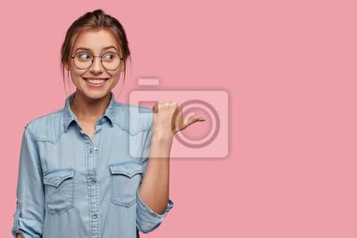 Image Jolie femme avec des conseils d'expression heureux utilise cet espace de copie à bon escient, vêtue d'une veste en jean à la mode, pointe avec le pouce de côté, modèles sur fond rose. Allez dans cette