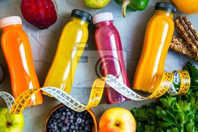 Jus rouges, orange, verts et jaunes, bouteilles de smoothies fraîches avec fruits et légumes, ruban à mesurer et barres de muesli, concept de mode de vie sain et végétalien