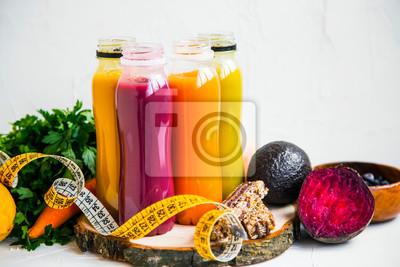 Jus rouges, oranges, verts et jaunes, bouteilles de smoothies fraîches avec légumes verts et frutis, ruban à mesurer et barres de muesli, concept de mode de vie sain et végétalien