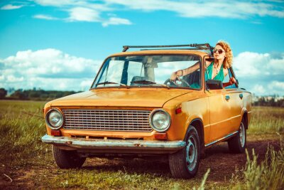 Image La femme est au volant d'une vieille voiture jaune. Milieu rural.