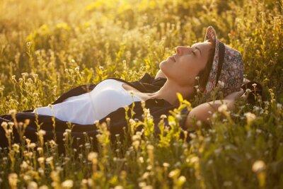 Image La fille dans un dremet de chapeau parmi les fleurs sauvages