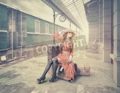 Image La jeune fille assise sur la valise d'attente à la rétro gare. Style de carte de couleur vintage