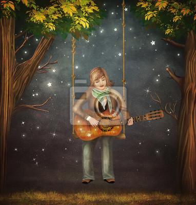 Le garçon est assis sur la balançoire dans la forêt et joue sur la guitare
