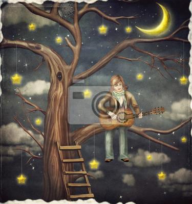 Le garçon est assis sur un arbre et joue sur la guitare