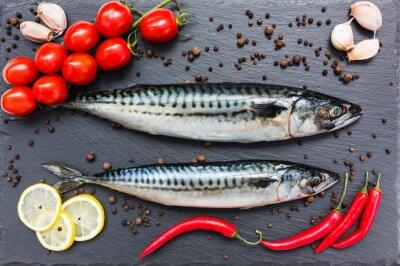 Image Le poisson frais du maquereau, le piment, citron, les tomates, l'ail sur une planche à découper en ardoise. Vue de dessus