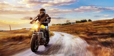 Image lecteurs de moto sur la route ouverte au coucher du soleil
