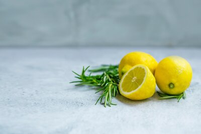 Lemons and rosemary branches on grey concrete background