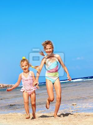 Les enfants se tenant la main en cours d'exécution sur la plage.
