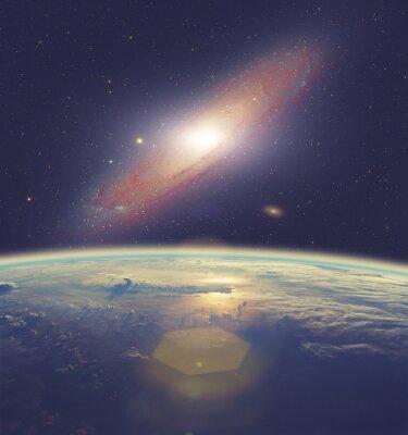 Image Lever de soleil sur la Terre avec une grande galaxie d'Andromède.
