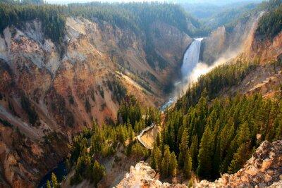 Image Lower Falls - La lumière du soleil illumine la pulvérisation alors que la rivière Yellowstone s'écrase au-dessus des chutes inférieures dans le Grand Canyon de Yellowstone.