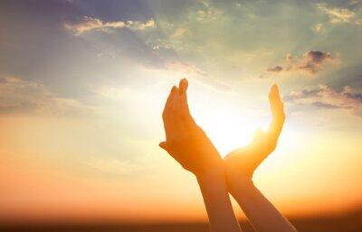 Image mains tenant le soleil à l'aube