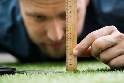 Image Man Using Measuring Scale While Cutting Grass