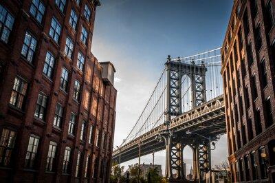 Image Manhattan Bridge vu depuis une ruelle étroite délimitée par deux bâtiments de brique sur une journée ensoleillée en été