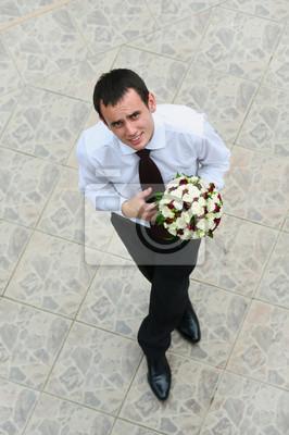 marié avec le bouquet de mariage debout et en regardant vers le haut