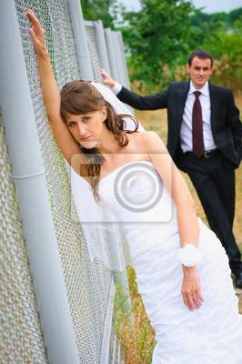Mariée de beauté en robe blanche debout près de la clôture. Groom derrière