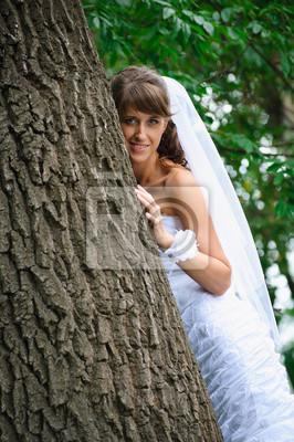 mariée de sourire en robe blanche debout près de l'arbre