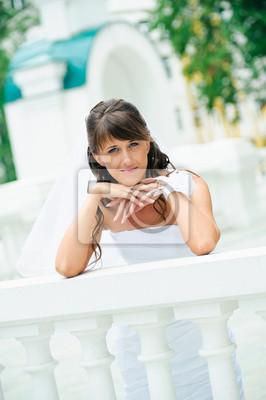 mariée pensive dans la robe blanche a penché sur les coudes main courante