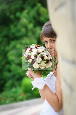 Mariée songeuse en robe blanche debout et tenant bouquet de roses