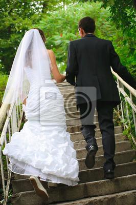 mariés marcher jusqu'à un escalier et se tenant les mains. backview