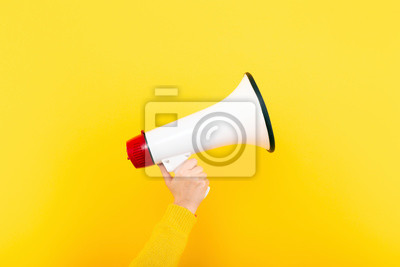 Image megaphone in hand on a yellow background, attention concept announcement