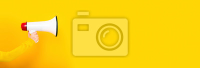 Image megaphone in hand on a yellow background, panoramic image, attention concept announcement