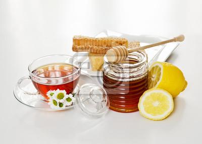 Miel avec alvéoles et une tasse de thé
