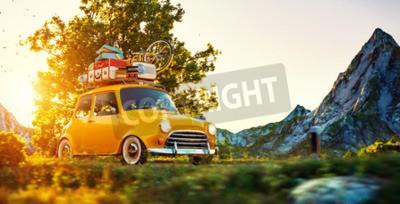 Image Mignon petite voiture rétro avec des valises et du vélo sur le dessus passe par la magnifique route de campagne au coucher du soleil