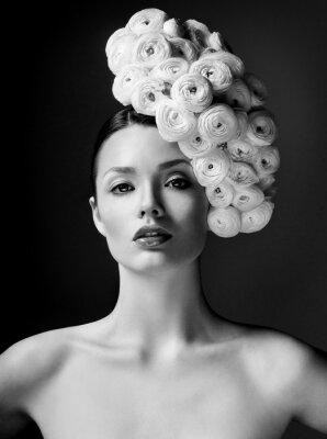 Image modèle de mode avec une grande coiffure et des fleurs dans ses cheveux.