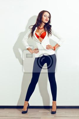 modèle sexy posant sur un mur blanc