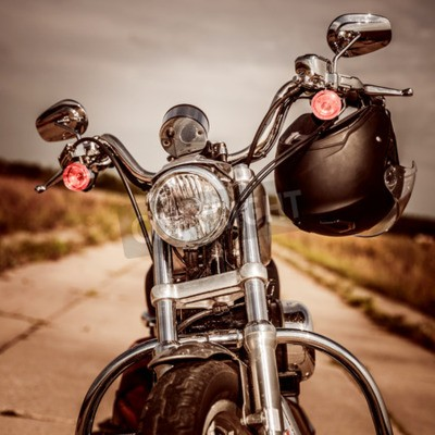 Image Moto sur la route avec un casque sur le guidon.